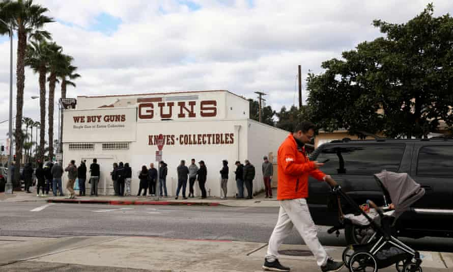 A pedestrian pushes a stroller as people wait in line outside to buy supplies at the Martin B Retting gun store amid fears of the global growth of coronavirus cases, in Culver City, California, on 15 March.