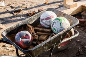 Footballs in a wheelbarrow ready for use. Young people play football in the camp's 100m buffer zone