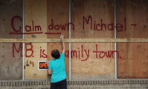 """A woman spray paints the words """"Calm down Michael"""" on the plywood over her daughter's business in preparation for the arrival of Hurricane Michael in Mexico Beach, Florida."""