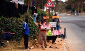 Job seekers in Johannesburg hold up placards at the roadside advertising their skills. South Africa unexpectedly fell into recession in the second quarter.