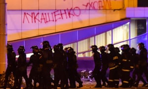 Riot police walk past a building with 'Lukashenko go away!' written on the wall during a protest against Lukashenko.