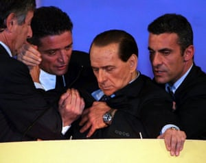 """November 2006: Berlusconi is supported at the podium by his personal doctor Umberto Scapagnini (left) as he slumps during an emotional speech to political supporters in Montecatini Terme. After 40 minutes of railing against the government of the then prime minister, Romano Prodi, Berlusconi suddenly started speaking slowly, looked weak and told the crowd: """"Emotion is getting the better of me. I …"""""""