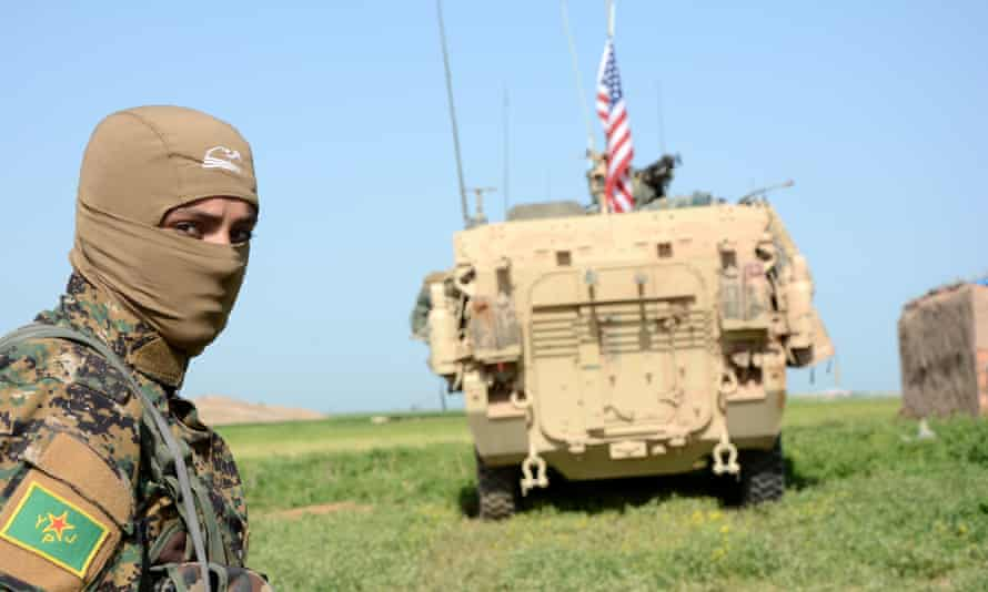 A YPG fighter stands near a US armoured vehicle, patrolling near al-Darbasiyah town at the Syrian-Turkish border.