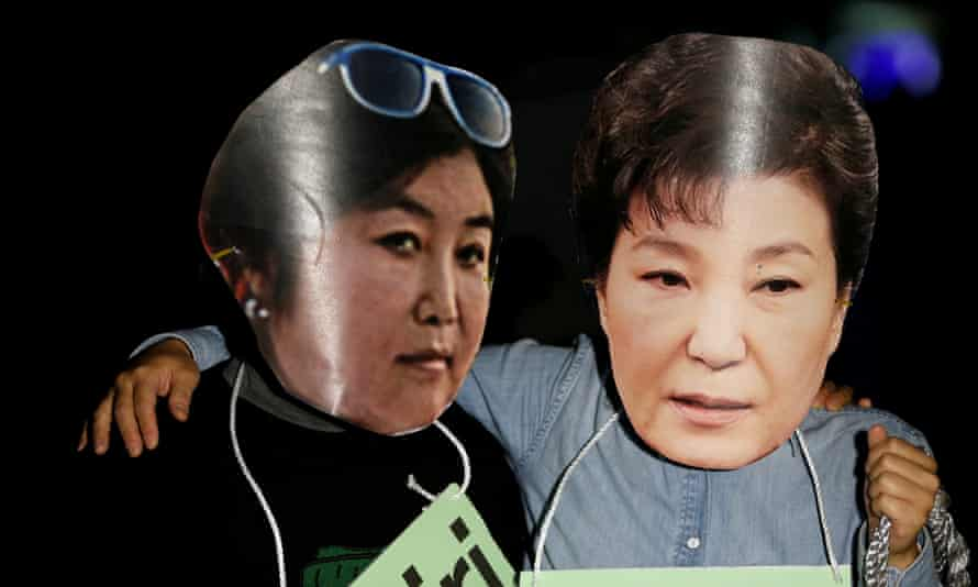 Protesters wearing cut-outs of South Korean president Park Geun-hye and Choi Soon-sil
