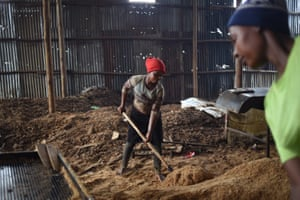 In Kampala, women shovel and sort sawdust (from scrap wood) to make briquettes