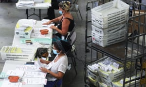 Election workers at the Orange county Registrar of Voters process stacks of mail-in ballots.