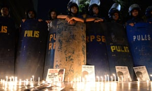 Anti-riot policemen stand next to lit candles and portraits of Filipina Mary Jane Veloso, as activists hold a vigil in front of the Indonesian embassy in Manila.