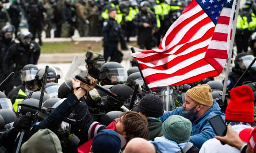 Trump supporters fight with riot police outside the Capitol building on 6 January.