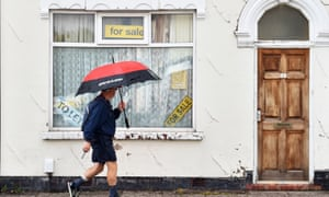 A man walks past a house with a 'For Sale' in Stoke-on-Trent