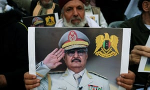 A protester carries a picture of Khalifa Haftar in Benghazi, Libya, April 2019