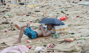 A tourist surrounded by rubbish on a beach in China. The country has struggled to contain environmental pollution during its long economic boom.
