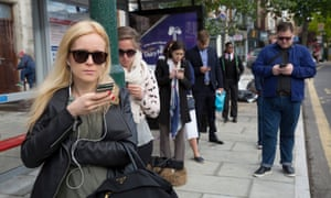 People looking at their mobile phones while waiting for the bus