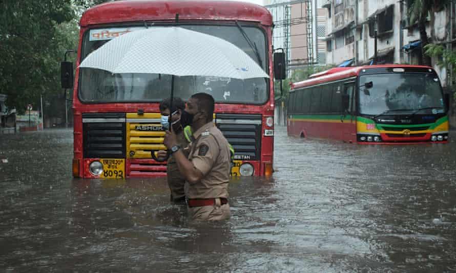 یک پلیس به راننده حمل و نقل عمومی کمک می کند تا از یک خیابان پر آب در بمبئی عبور کند.