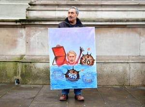 Artist Kaya Mar holds one of his paintings outside Downing Street.