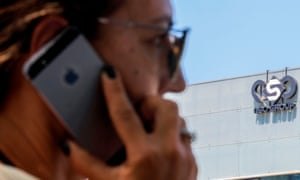 An Israeli woman uses her iPhone in front of the building housing the Israeli NSO group's offices in Herzliya, near Tel Aviv.