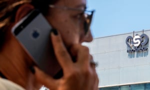 An Israeli woman uses her iPhone in front of the building housing the Israeli NSO Group in Herzliya, near Tel Aviv.