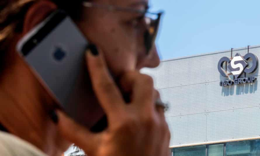 A woman uses her iPhone in front of the building housing the Israeli NSO group, in Herzliya, near Tel Aviv.