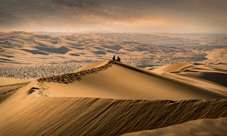 A couple sitting on the top of a giant sand dune in the desert watching the sunset in the Empty Quarter, or Rub al Khali, the world's largest sand desert