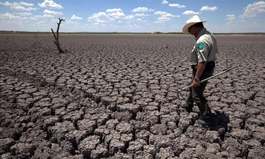 Texas State Park police officer Thomas Bigham walks across the cracked lake bed of O.C. Fisher Lake Wednesday, Aug. 3, 2011, in San Angelo, Texas. Heat and drought dried up the lake that once spanned over 5400 acres.