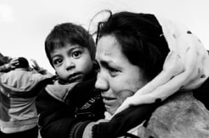 An Afghan mother cries with relief while clasping her child