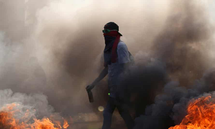 A demonstrator walks while building a fire on the street during a rally in Caracas.