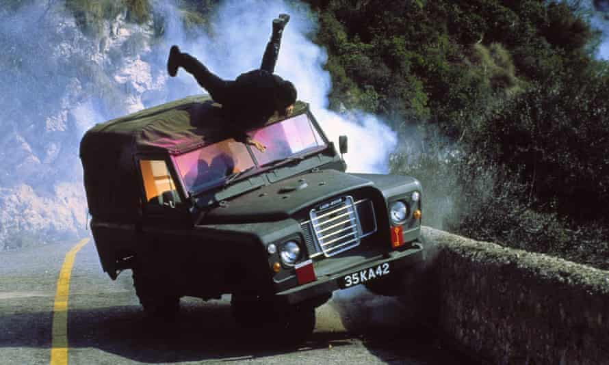 James Bond clings to the top of a Land Rover in a scene from The Living Daylights