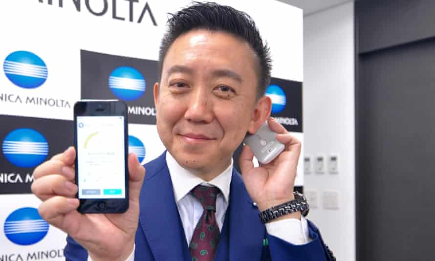 Daisuke Koda, from Konica Minolta, demonstrates the use of the Kunkun body odour checker behind the ear. The results show up on a smartphone app via Bluetooth.