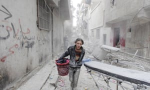 A boy carries his belongings after an apparent barrel bomb strike in Aleppo