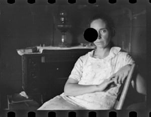 Woman in chair, face partly obscured by black circle