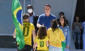 Brazilian President Jair Bolsonaro and his daughter Laura (R) greet supporters outside Planalto Palace in Brasilia.