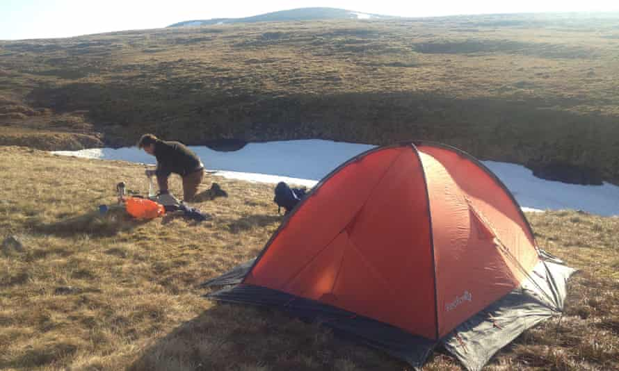 Writer Caroline Eden's husband setting up a tent for wild camping in the Cairngorms, Scotland, UK.