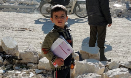 A Syrian boy holds his books as he stands outside his school following airstrikes by Syrian government forces in the northern Syrian city of Marea, on the outskirts of Aleppo, in 2013.