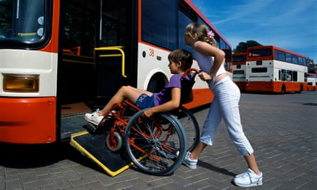 A boy in a wheelchair is helped onto a bus