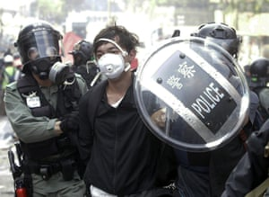 Police officers detain a protester