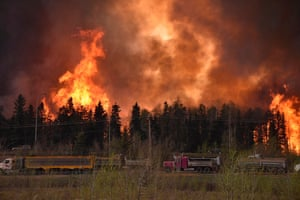 Wildfire rages as lorries pass by on Highway 63 in Canada