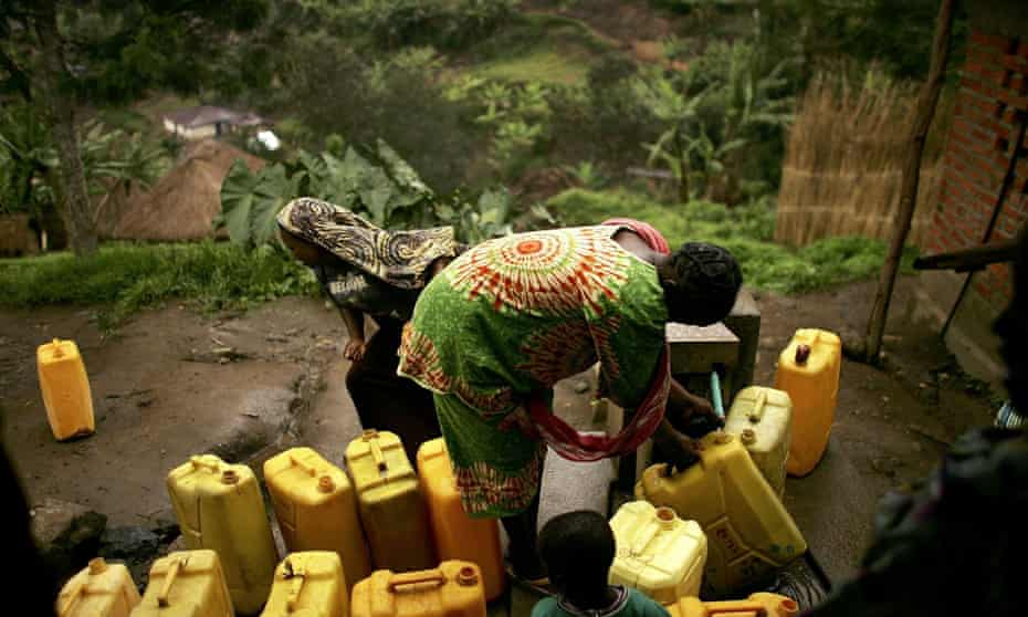 Women fill jugs of water from a tap  in Kaynabayonga, DRC
