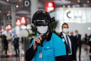 An employee wearing a thermal imaging VF helmet monitors passengers at the entrance of Istanbul airport.