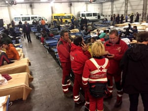 Rescuers assist people sheltering in a bus hangar in Camerino.