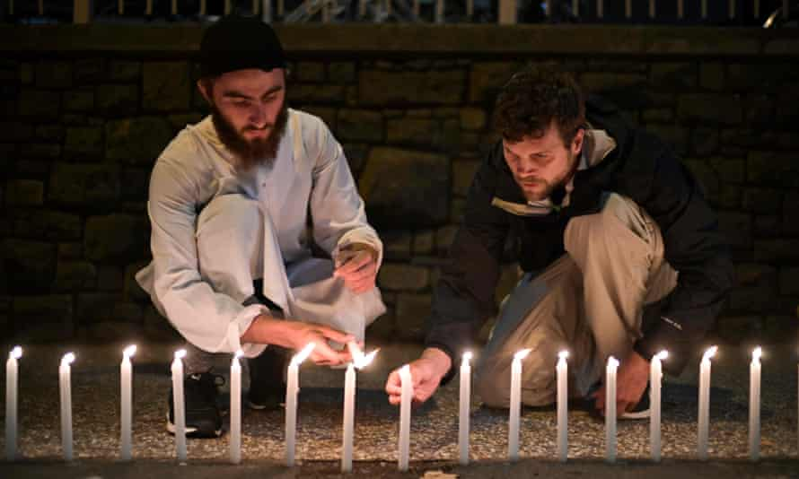 Two men light candles outside the hospital in Christchurch on Saturday