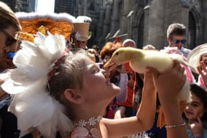 NEW YORK, NY A young woman holds a duck while wearing a feathered headpiece during the Easter Parade and Bonnet Festival along 5th Avenue
