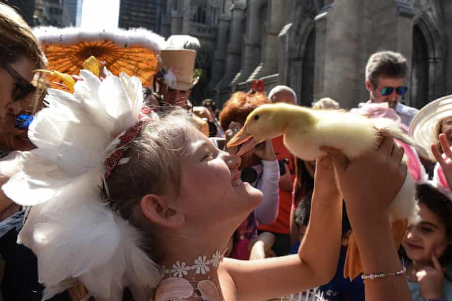 A woman holds a duck at the Easter Parade and Bonnet festival on 5th Avenue, New York City, in April