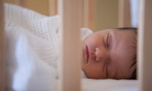 A sleeping baby in a cot