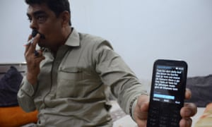 Police officer Shoaib Sheikh – nicknamed Shoaib Shooter – who admits to killing scores of militants, shows a death threat texted to his mobile.