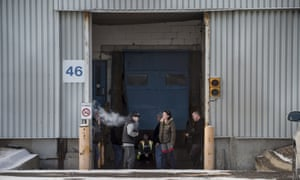 Workers take a smoke break on their last day outside the GM plant in Oshawa, Ontario, on 18 December.