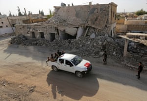 Free Syrian Army fighters ride on a pickup truck decorated with a Turkish flag past damaged buildings in the rebel-held town of al-Rai, in Aleppo governorate