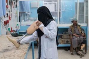 Fayda Ali Ali, a nurse trained in prosthetics, adjust a limb in the orthopaedic ward of a hospital in Marib, Yemen on 20 February 2018