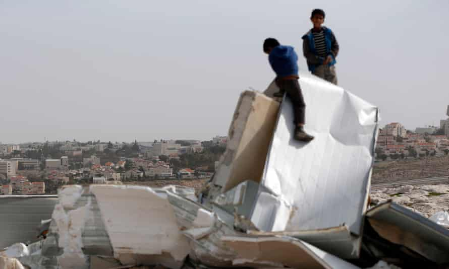 Palestinian Bedouin boys climb on the remains of their makeshift homes near al-Azariya, on the West Bank. The Israeli army said it demolished the homes as they were built illegally. The illegal Jewish settlement of Maale Adumin is seen in the background.