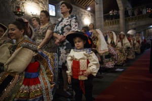 Women and a young boy attend mass in their costumes