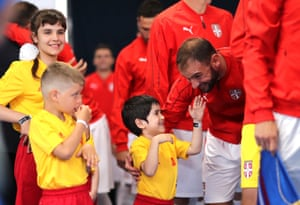 Branislav Ivanovic of Serbia lets a young mascot tickle his beard.