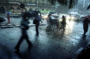 People with umbrellas in rain in Mumbai at night